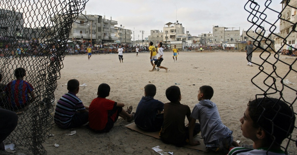 28.jul.2012 - Jovens palestinos assistem jogo de futebol local, neste s&#225;bado (28),  pouco antes do p&#244;r do sol, em um campo de refugiados em Rafah, no sul da Faixa de Gaza, durante o Ramad&#227;, m&#234;s sagrado mu&#231;ulmano. Os mu&#231;ulmanos de todo o mundo se abst&#233;m de comida, bebida e rela&#231;&#245;es sexuais do nascer ao p&#244;r do sol  