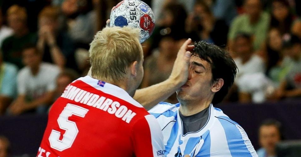Argentino Juan Manuel Vázquez leva um tapa em disputa de bola com islandês neste domingo (29/07)