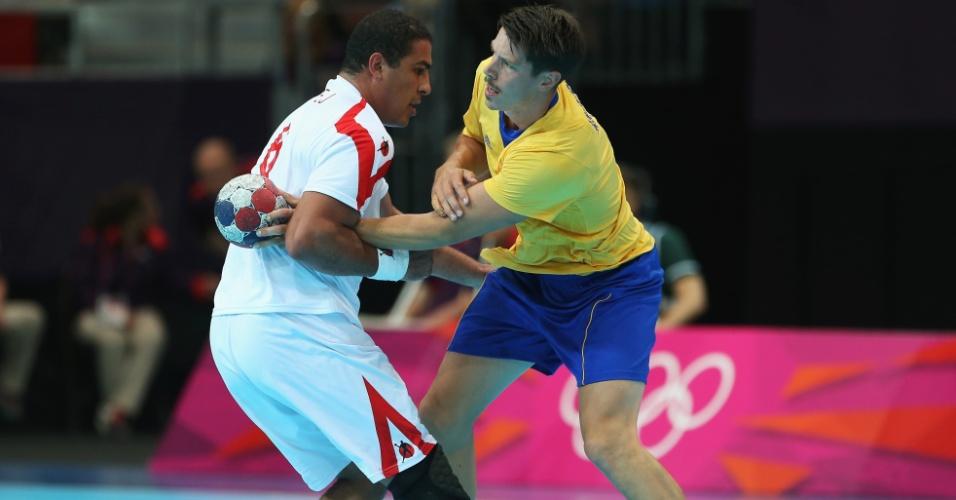 Issam Tej, da Tunísia, agarra braço de Kim Andersson, da Suécia, em jogo disputado neste domingo (29/07)