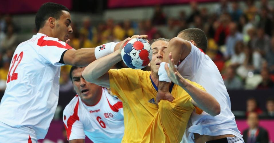 Jogadores da Tunísia seguram Kim Ekdahl du Rietz, da Suécia, em jogo disputado neste domingo (29/07)