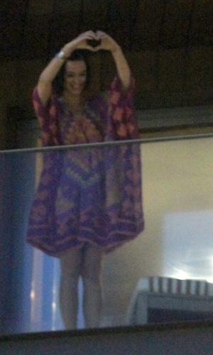Katy Perry sai na sacada de seu quarto no Rio e faz coração com as mãos para seus fãs (29/7/12)