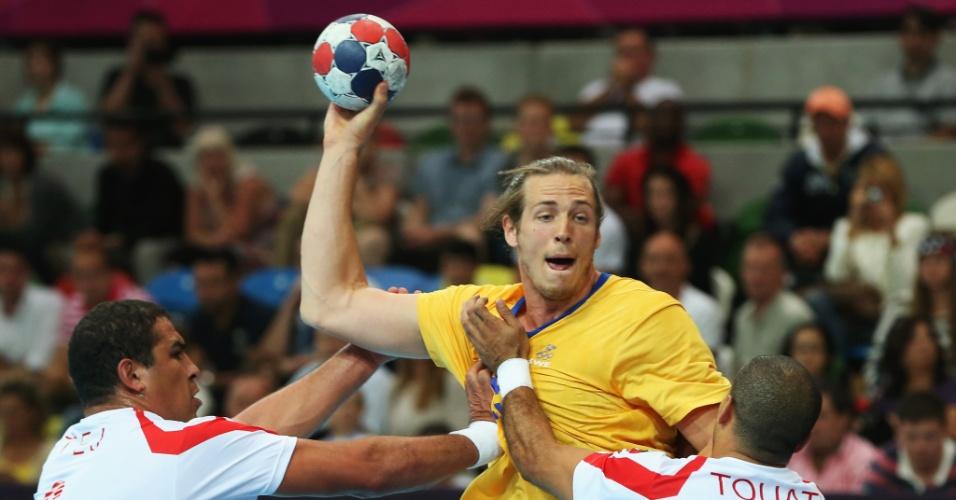 Kim Ekdahl du Rietz, da Suécia, é agarrado por jogadores da Tunísia em partida neste domingo (29/07)