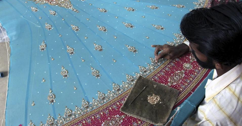 30.jul.2012 - Artesão decora vestimenta típica durante os preparativos para a festa de Eid Ul-Fitr, que marca o final do mês do Ramadã, em Karachi, no Paquistão