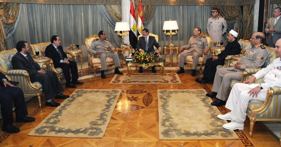 30.jul.2012 - O presidente do Egito, Mohamed Mursi (centro), recebe convidados das Forças Armadas do país para uma cerimônia de Iftar, a refeição em que os muçulmanos quebram o jejum do Ramadã, no início da noite. A foto é do domingo (29), em um clube militar do Cairo