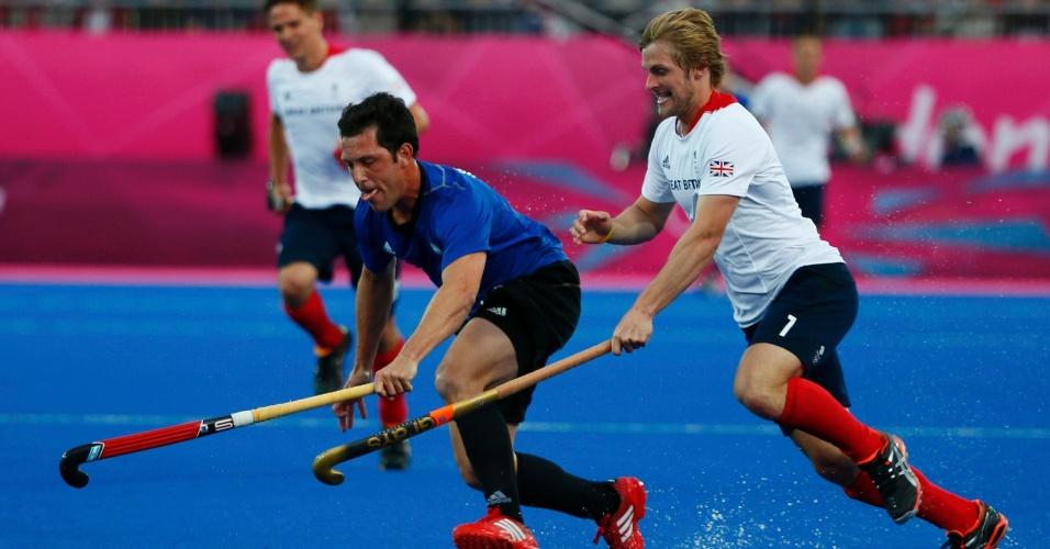 Argentino Pedro Ibarra disputa bola com britânico Ashley Jackson em partida do hóquei masculino