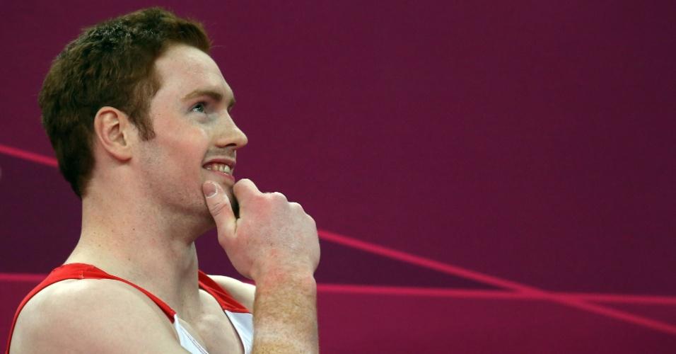Ginasta britânico Daniel Purvis sorri durante competição por equipes masculina