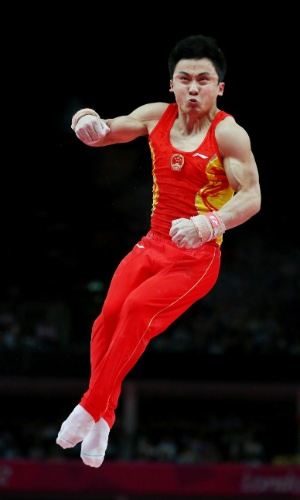 Ginasta chinês Zhe Feng faz biquinho durante prova das argolas na final masculina por equipes