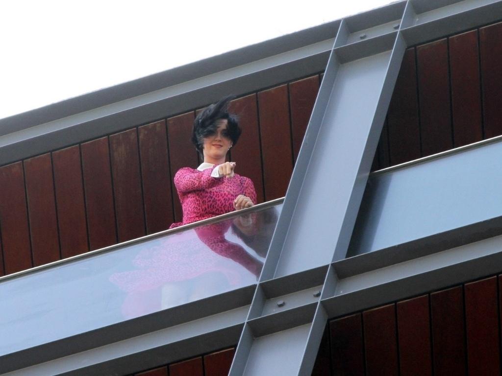 Na sacada do hotel em que está hospedada no Rio de Janeiro, Katy Perry interage com os fãs, que vão ao delírio (30/7/12)