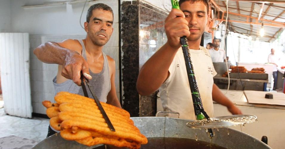 31.jul.2012 - Em Boufarik, no sul de Argel (capital da Argélia), homens preparam doce durante festa do mês sagrado do Ramadã