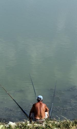31.jul.2012 - Homem pesca em lago artificial no vilarejo de Mbreshtan, próximo ao município de Berat, na Albânia. A população albanesa enfrenta dias de calor e com temperatura em torno de 40°C