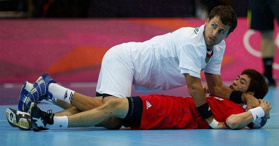 Húngaro Tamas Mocsai tromba com o sul-coreano Jeong Han durante partida de handebol na Olimpíada de Londres e ambos ficam no chão (31/07/2012)