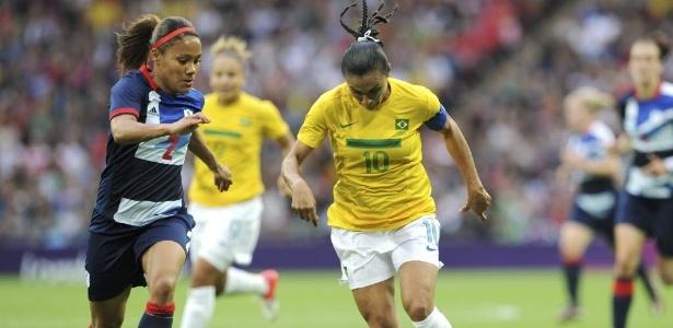 Marta, camisa 10 da seleção brasileira, conduz a bola cercada de perto pela britânica Alex Scott