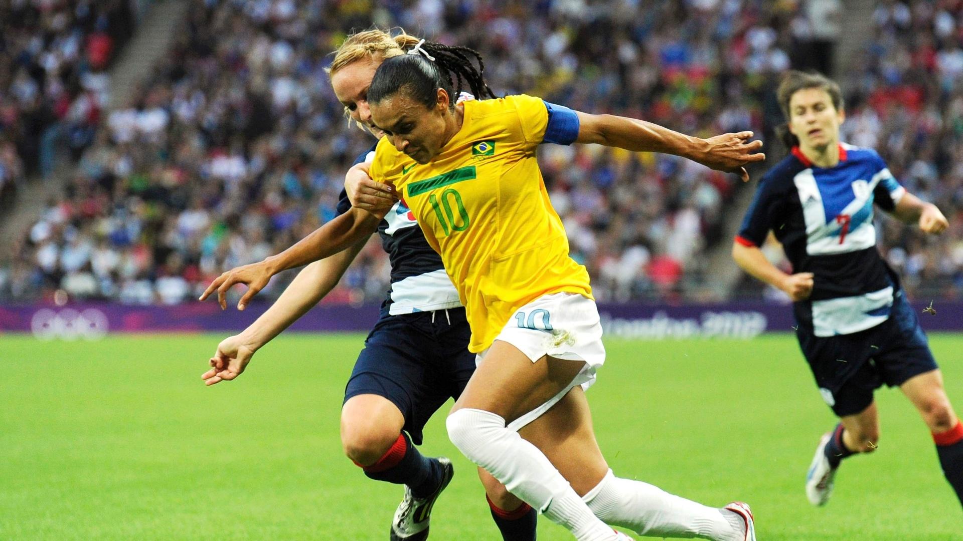 Marta tenta escapar da marcação de jogadora britânica na partida entre Brasil e Reino Unido no estádio Wembley