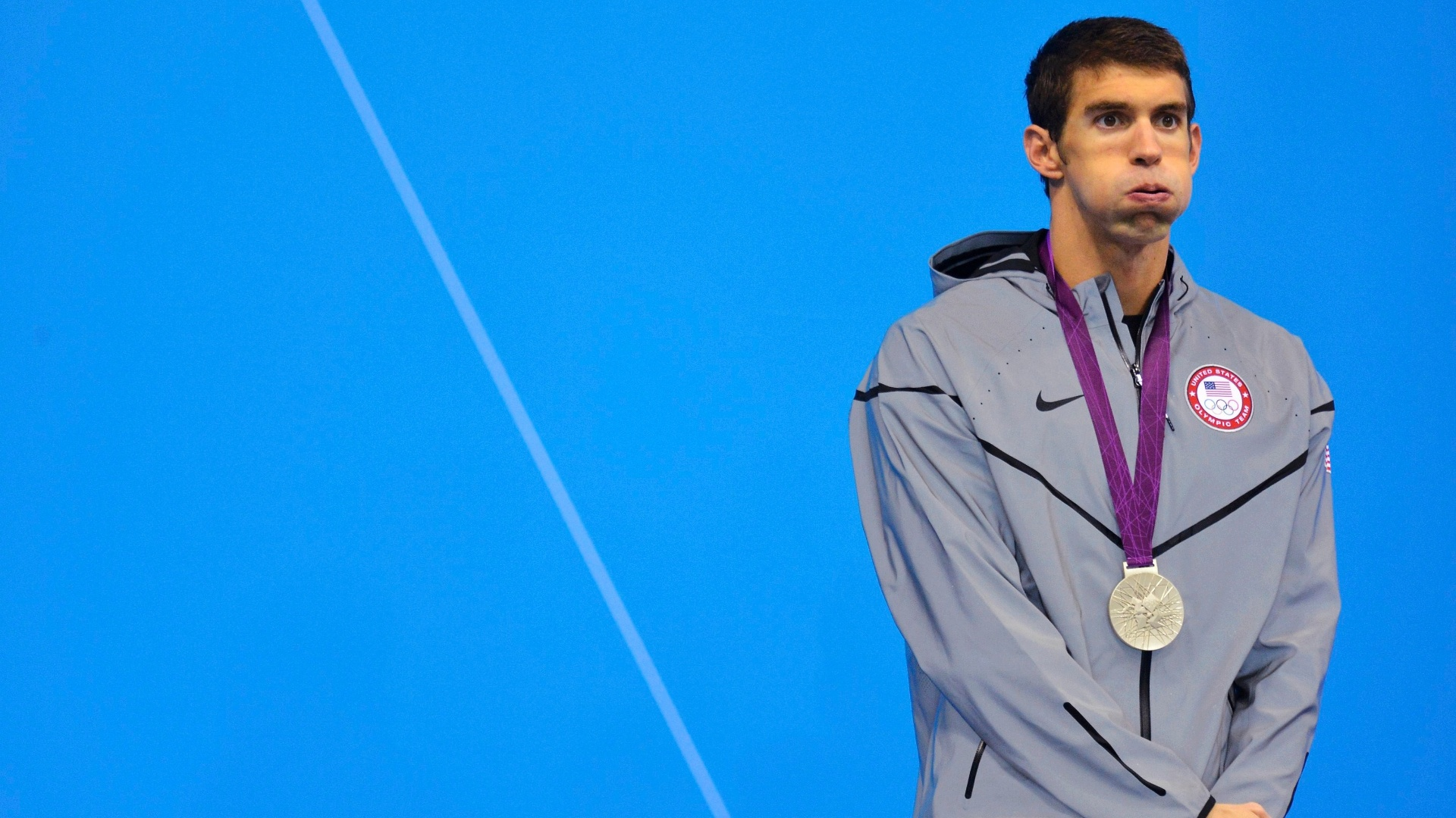 Michael Phelps parece cansado enquanto recebe a medalha de prata na natao