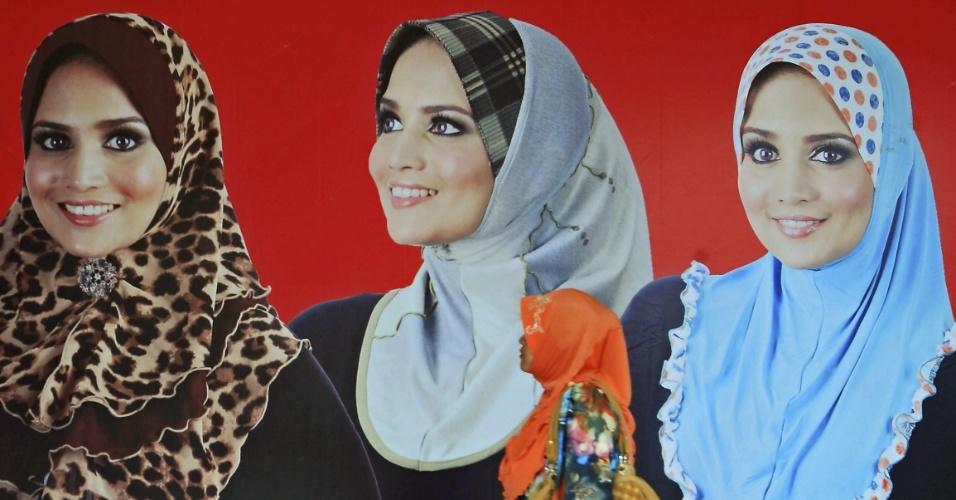 1º.ago.2012 - Mulher passa por outdoor com as últimas tendências em hiyabs, véus para cobrir a cabeça das muçulmanas, em Shah Alam, na Malásia, perto da capital, Kuala Lumpur. As lojas já começaram a anunciar presentes para a festa de Eid-el-Fitr, que marca o fim do Ramadã