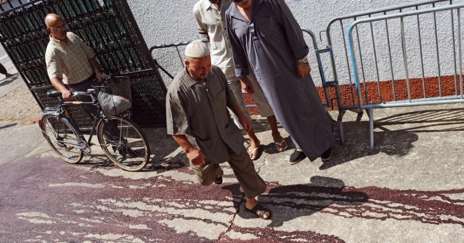 1º.ago.2012 - Pessoas passam por uma calçada manchada por sangue de porco em frente a uma mesquisa em Montauban, no sul da França. Fieis que chegaram para as orações da manhã fincaram duas cabeças de porco no portão da mesquita, nesta quarta-feira (1)