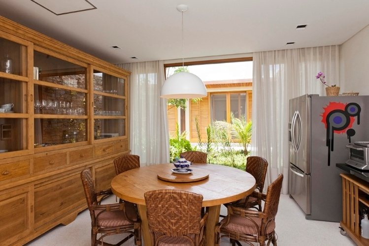A sala de almoço da Casa H tem mobiliário de madeira clara que acompanha o tom das esquadrias. O projeto arquitetônico da residência é assinado por Erick Figueira de Mello