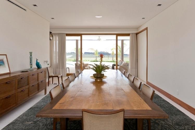 A sala de jantar da Casa H, no interior de São Paulo, acomoda 12 pessoas em uma ampla mesa de madeira. O ambiente foi decorado pelos próprios proprietários do imóvel