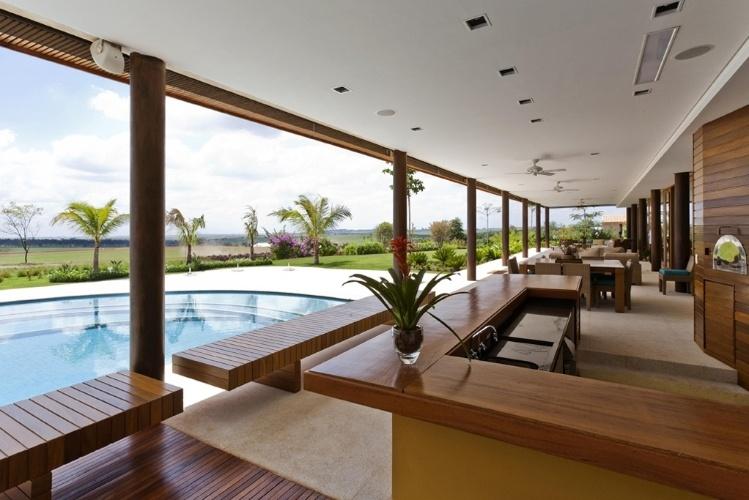A varanda da Casa H, no interior de São Paulo, abriga uma área gourmet, além de uma sauna. O ambiente externo está ligado às salas principais da residência projetada por Erick Figueira de Mello