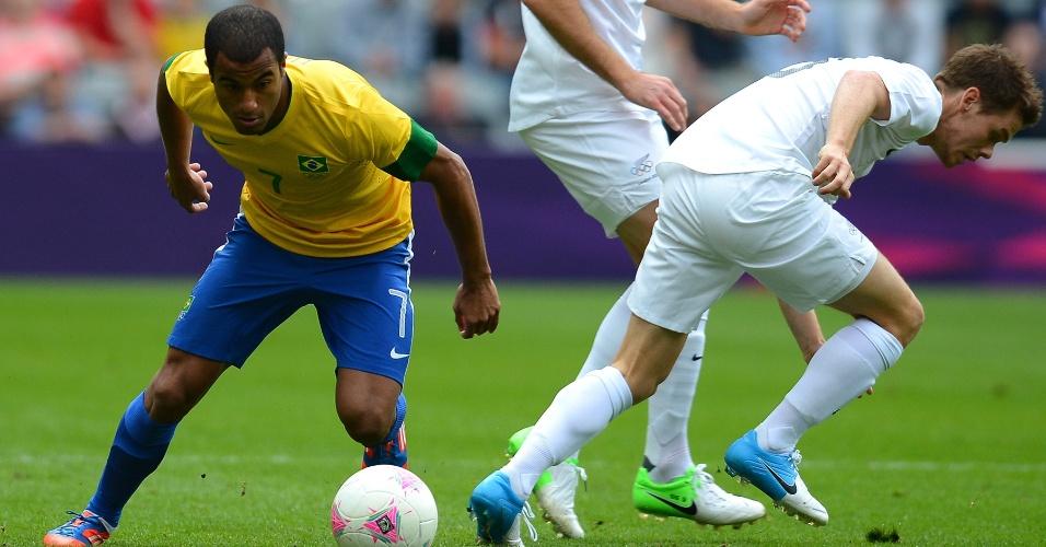 Com a bola dominada, Lucas passa pela marcação adversária no último jogo da seleção nesta primeira fase dos Jogos
