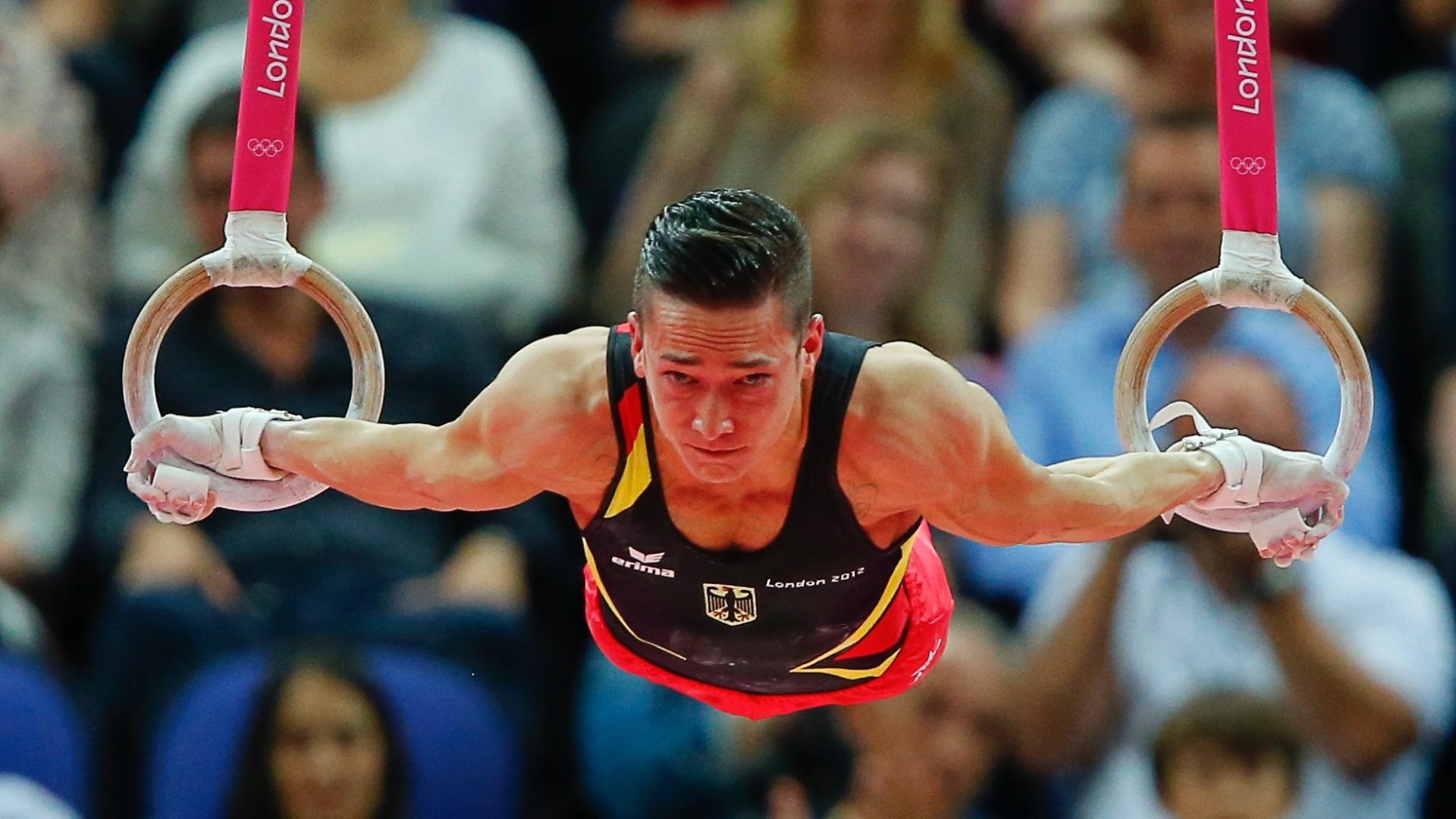 Ginasta alemão faz força para se sustentar nas argolas na final masculina de individual geral