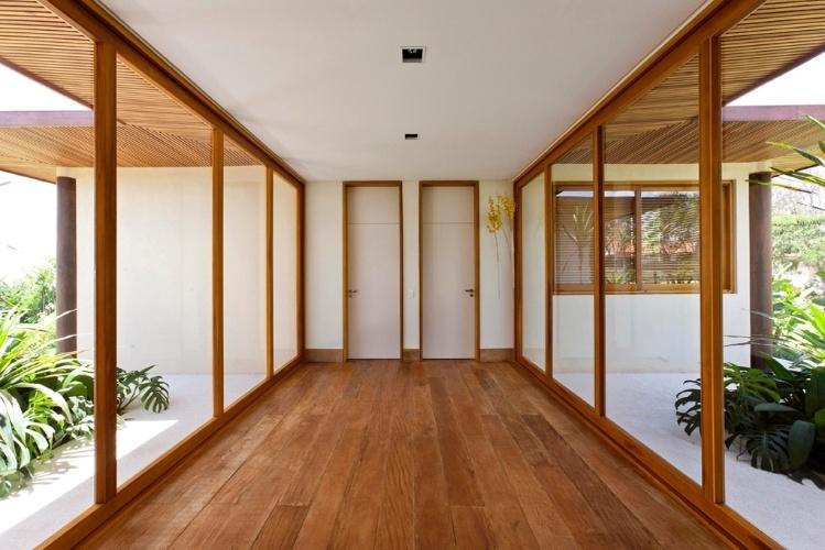 Vista do hall que interliga a ala íntima da casa com o bloco que reúne suíte e escritório. A Casa H, no interior do estado de São Paulo, possui áreas internas e jardins (inclusive um lago) integrados