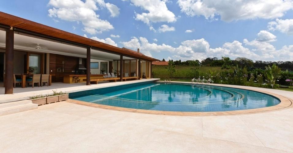 Junto à varanda e um extenso gramado, a piscina da Casa H está no limite da área construída que conta com generosos 1.100 m². O projeto de arquitetura é de Erick Figueira de Mello