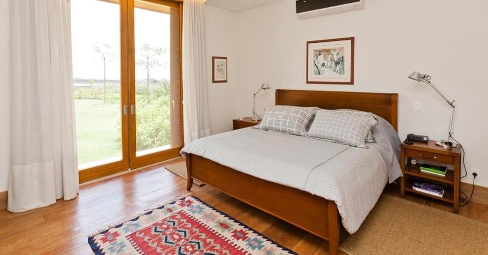 Em um dos quartos da Casa H, luminárias do modelo Tolomeo, da Wall Lamps, estão apoiadas sobre mesas de cabeceira feitas de madeira clara, do mesmo tom da usada na cama e das esquadrias