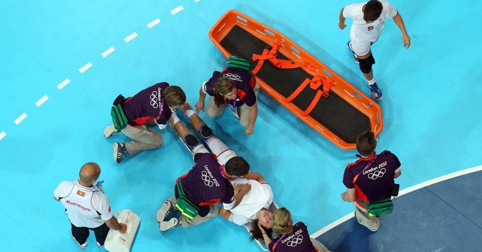 01.ago.2012 - Montenegrina Milena Knezevic é retirada de maca após se machucar em partida contra Angola