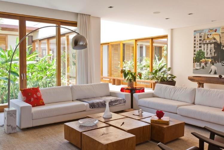 No estar da Casa H, assinada por Erick Figueira de Mello, as mesas baixas de madeira são combinadas com sofás de tecido em tom cru. As portas de vidro e madeira da Mado e possibilitam a vista dos jardins
