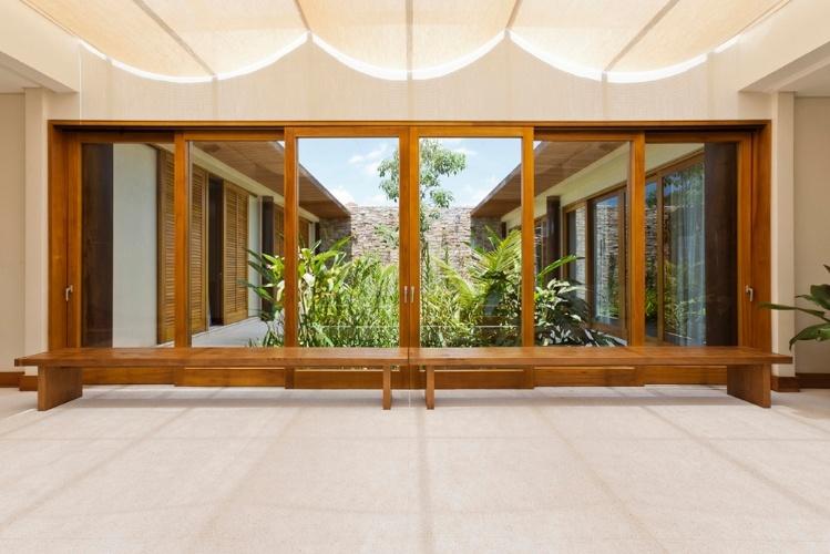 """O hall que liga os dois """"braços"""" da Casa H tem amplas portas envidraçadas com esquadrias de madeira da Mado. No teto, cortes de linho filtram a luz natural que atravessa o pergolado de alumínio. O projeto é assinado por Erick Figueira de Mello"""