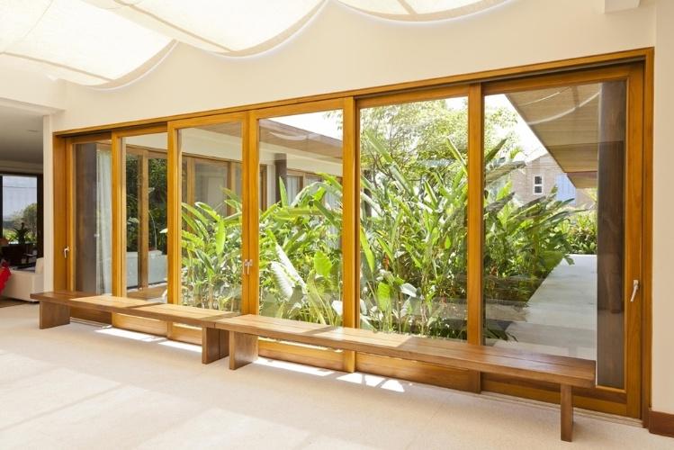 """O hall que liga os dois """"braços"""" da Casa H tem amplas portas envidraçadas com esquadrias da Mado. No teto, cortes de linho filtram a luz natural que atravessa o pergolado de alumínio. O projeto é assinado por Erick Figueira de Mello"""