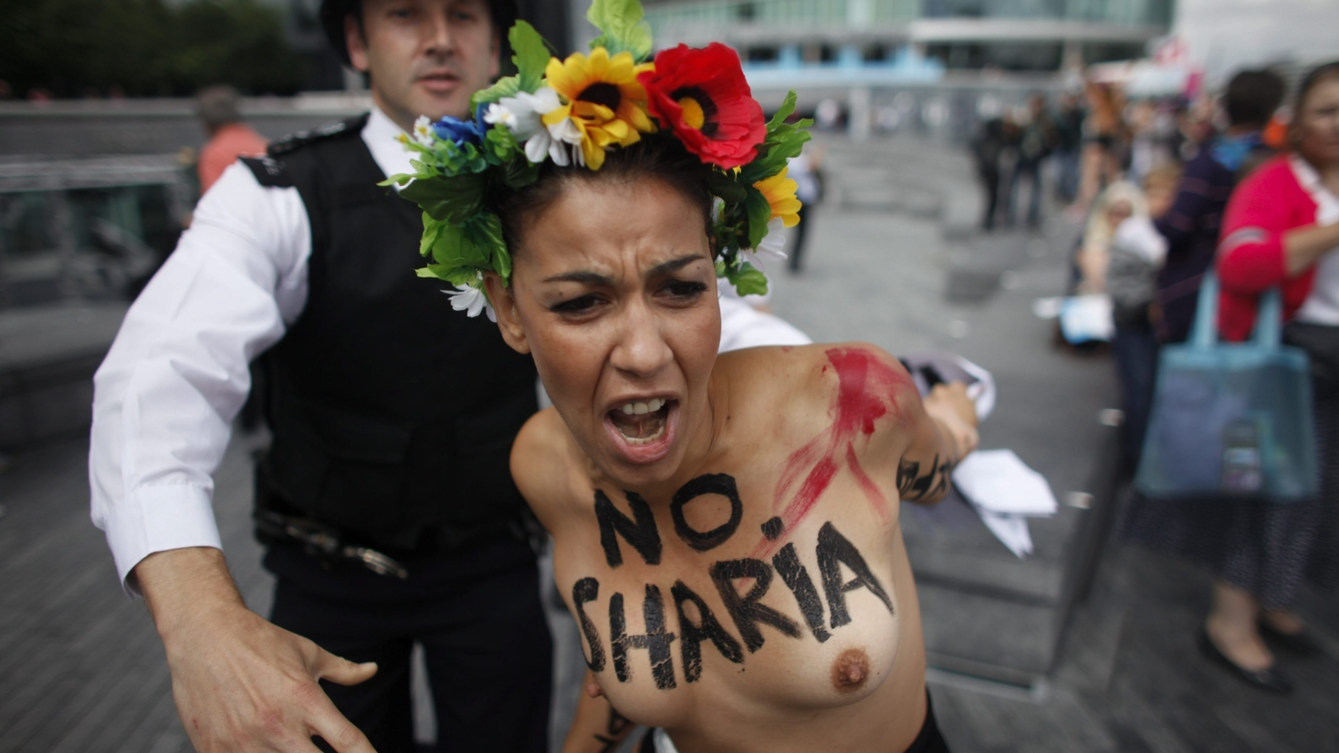 2.ago.2012 - Policiais britnicos prendem ativista do grupo Femen nesta quinta-feira (2) durante protesto em Londres, no Reino Unido, contra a aprovao dos regimes islmicos pelo comit olmpico