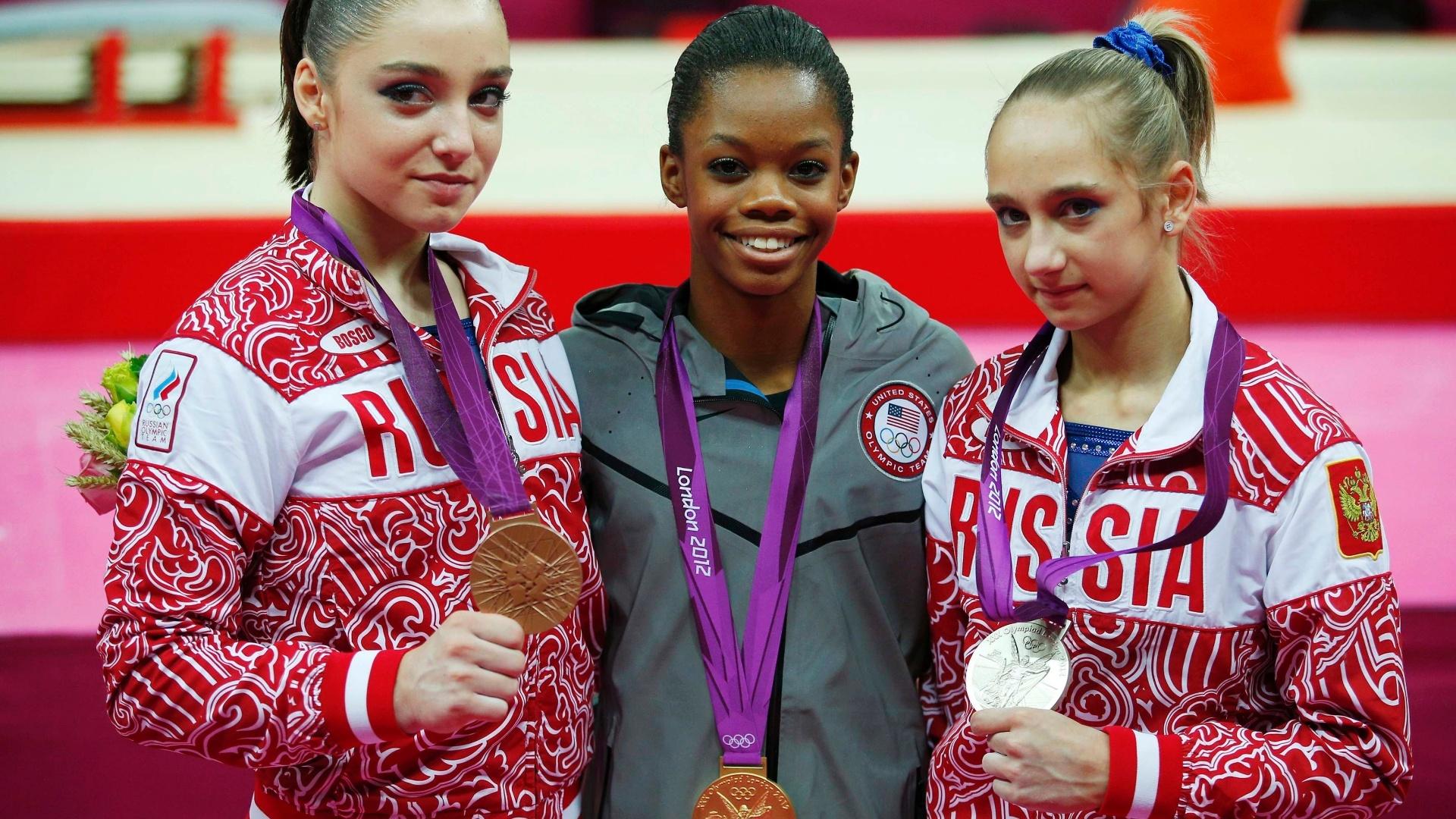 Aliya Mustafina (e), Gabby Douglas (c) e Victoria Komova mostram as medalhas de bronze, ouro e prata conquistadas por elas na final individual geral da ginástica artística