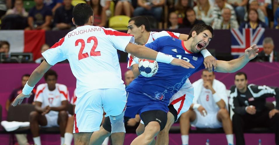 Francês Nikola Karabatic é derrubado pelos tunisianos em partida do handebol masculino