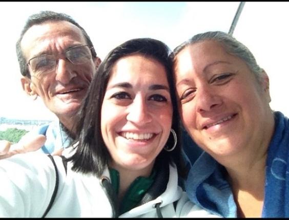 Ginasta Daniele Hypólito tira foto ao lado dos pais, após se participar dos Jogos Olímpicos.