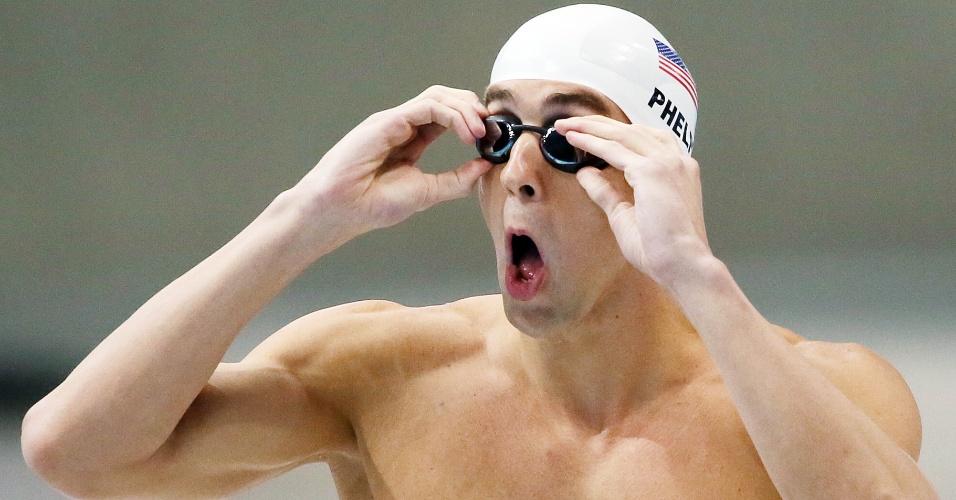 Michael Phelps faz careta enquanto ajeita seus óculos para eliminatória dos 100 m borboleta