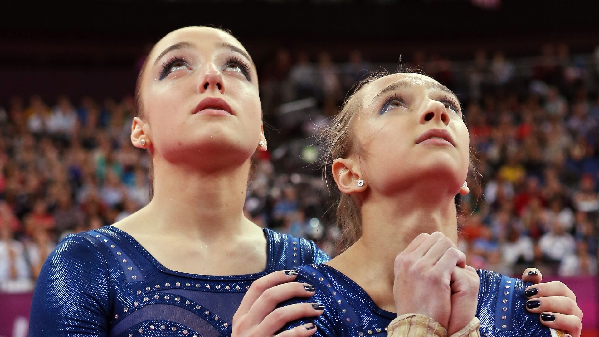 Russas Aliya Mustafina (e) e Victoria Komova mostram apreensão à espera da última nota da final desta quinta-feira; Komova ficou com a prata, e Mustafina levou o bronze