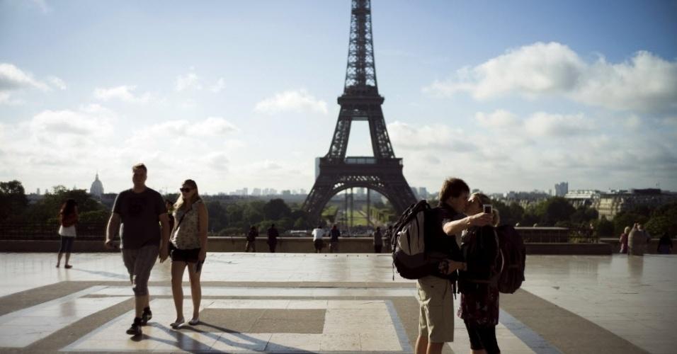 3.ago.2012 -  Casal se beija em Paris, na França, durante registro de foto, perto da famosa Torre Eiffel, nesta sexta-feira, em dia de calor na capital francesa
