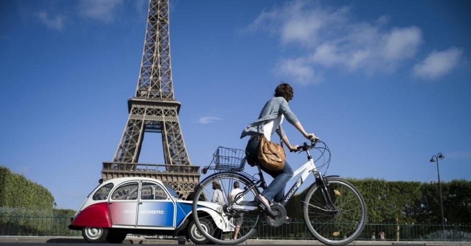 3.ago.2012 -  Ciclista pedala em Paris, na França, perto da famosa Torre Eiffel, em dia quente, nesta sexta-feira