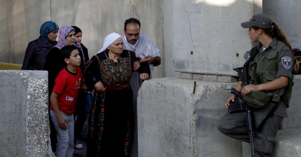 3.ago.2012 - Guarda israelense em fronteira com a Cisjordânia observa palestinos, nos arredores de Belém. Muçulmanos, esses palestinos se encaminham para Jerusalém para a terceira sexta-feira de rezas do mês sagrado do Ramadã