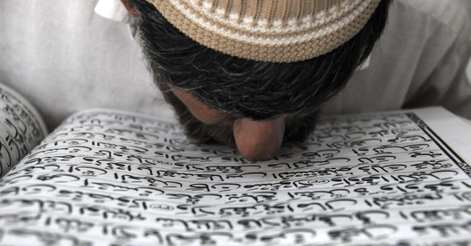 3.ago.2012 - Muçulmano beija as escrituras durante o mês do Ramadã, sagrado para os islâmicos, em Peshawar, no Paquistão