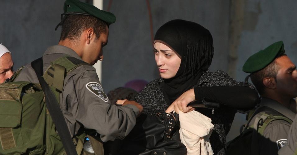 3.ago.2012 - Policial israelense revista a bolsa de uma mulher palestina que sai de Ramallah a caminho de Jerusalém, para visitar a mesquita Al-Aqsa