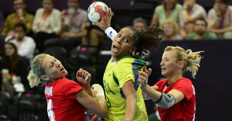Ana Paula, da seleção de handebol, tenta arremesso cercada por duas jogadoras da Rússia
