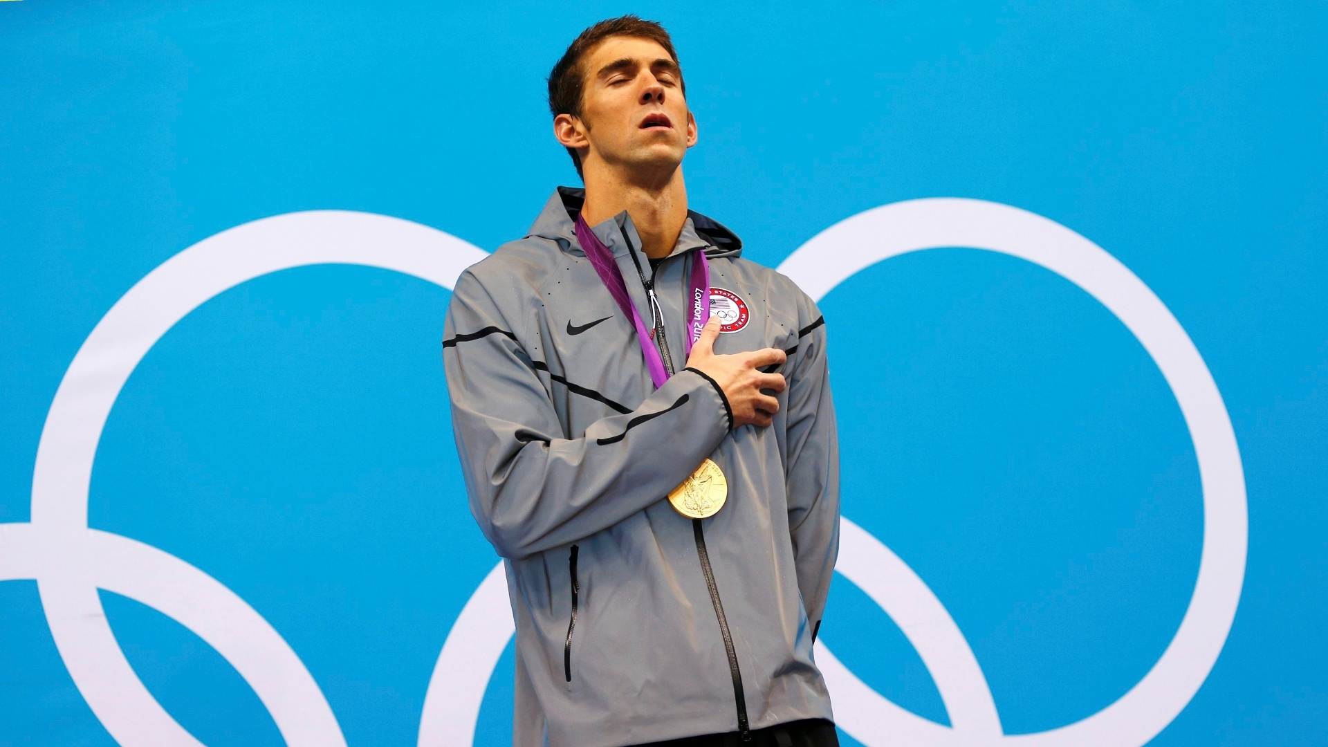 Nadador norte-americano Michael Phelps canta o hino durante a cerimnia de entrega das medalhas dos 100m borboleta