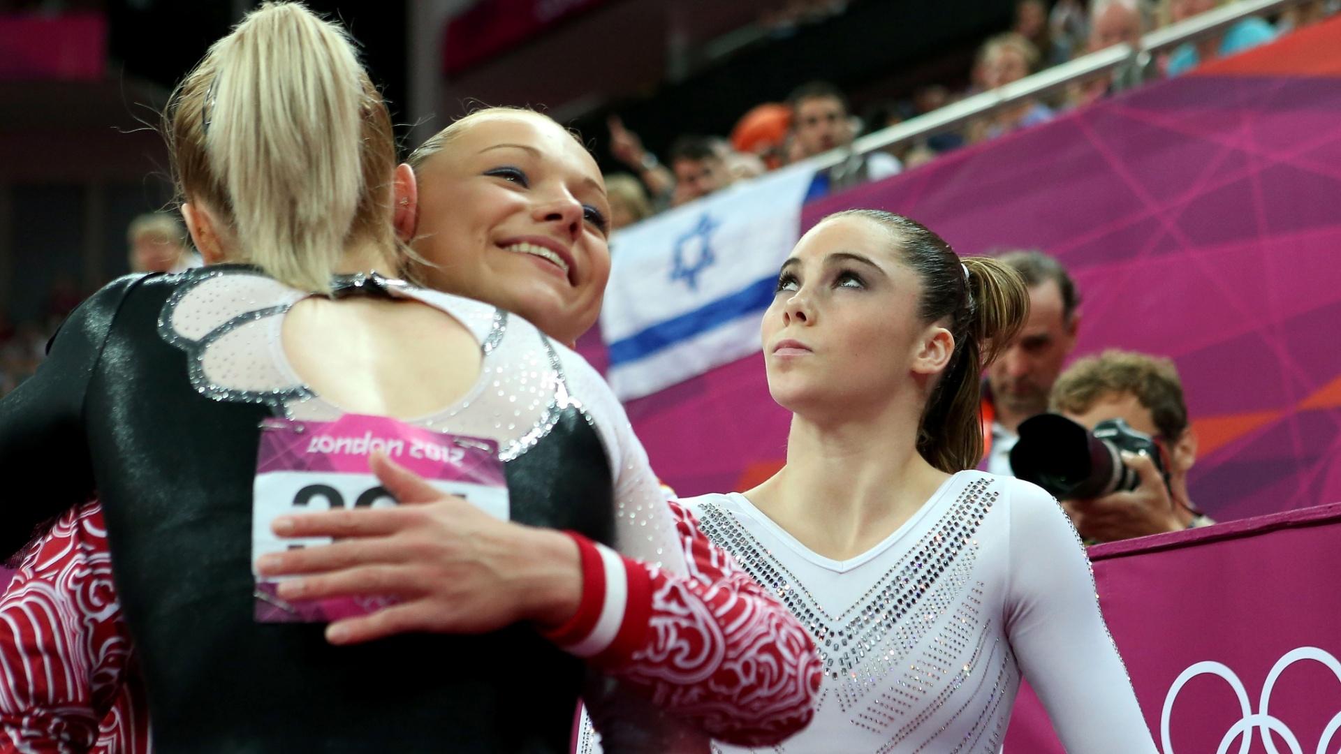 Campeã de salto Sandra Izbasa (de costas) recebe os cumprimentos da medalhista de bronze Maria Paseka enquanto a vice McKayla Maroney faz cara feia