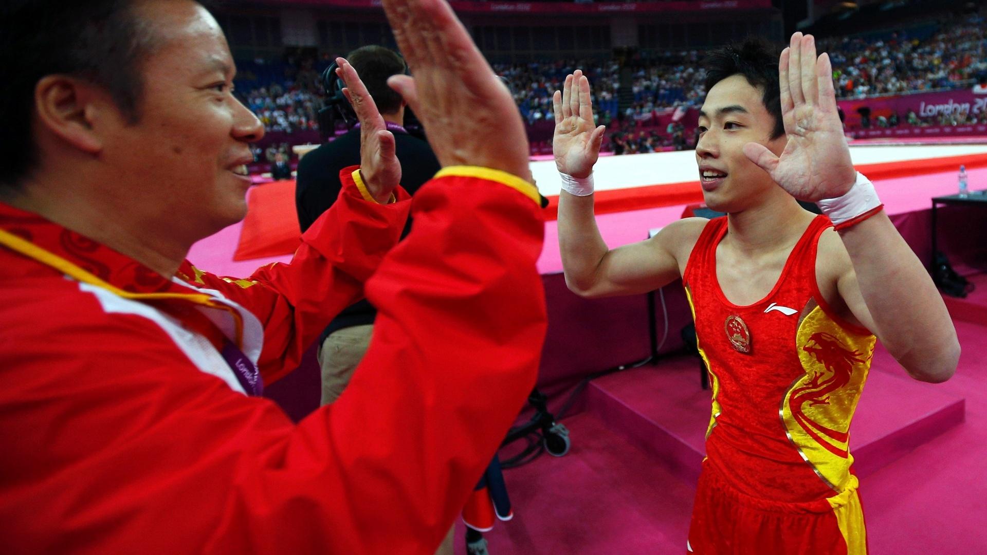 Chinês Zou Kai comemora com seu técnico ao conquistar a medalha de ouro da final de solo neste domingo em Londres