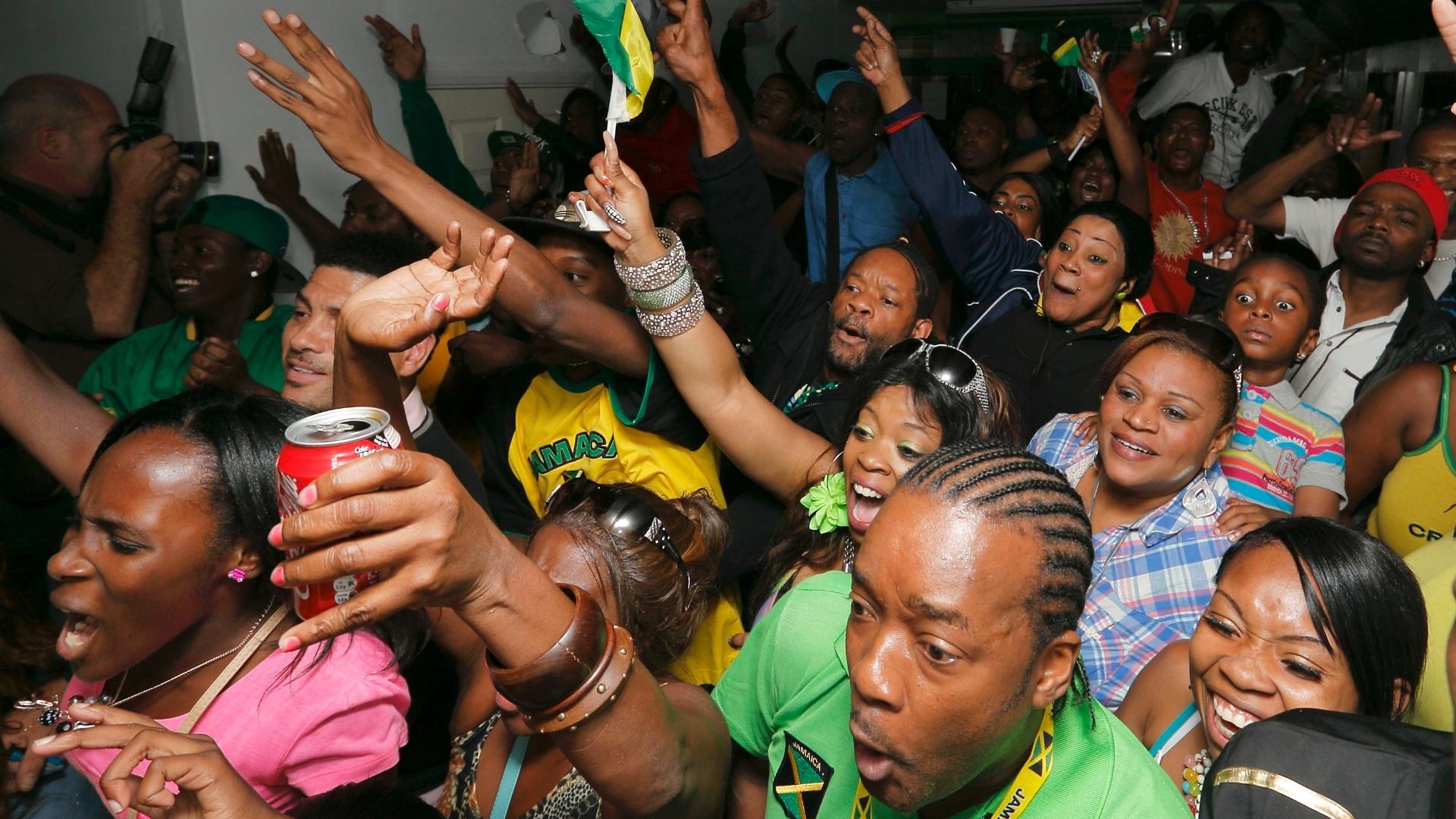 Espectadores da comunidade jamaicana em Brixton, ao sul de Londres, comemoram vitória de Usain Bolt na final olímpica dos 100 m rasos