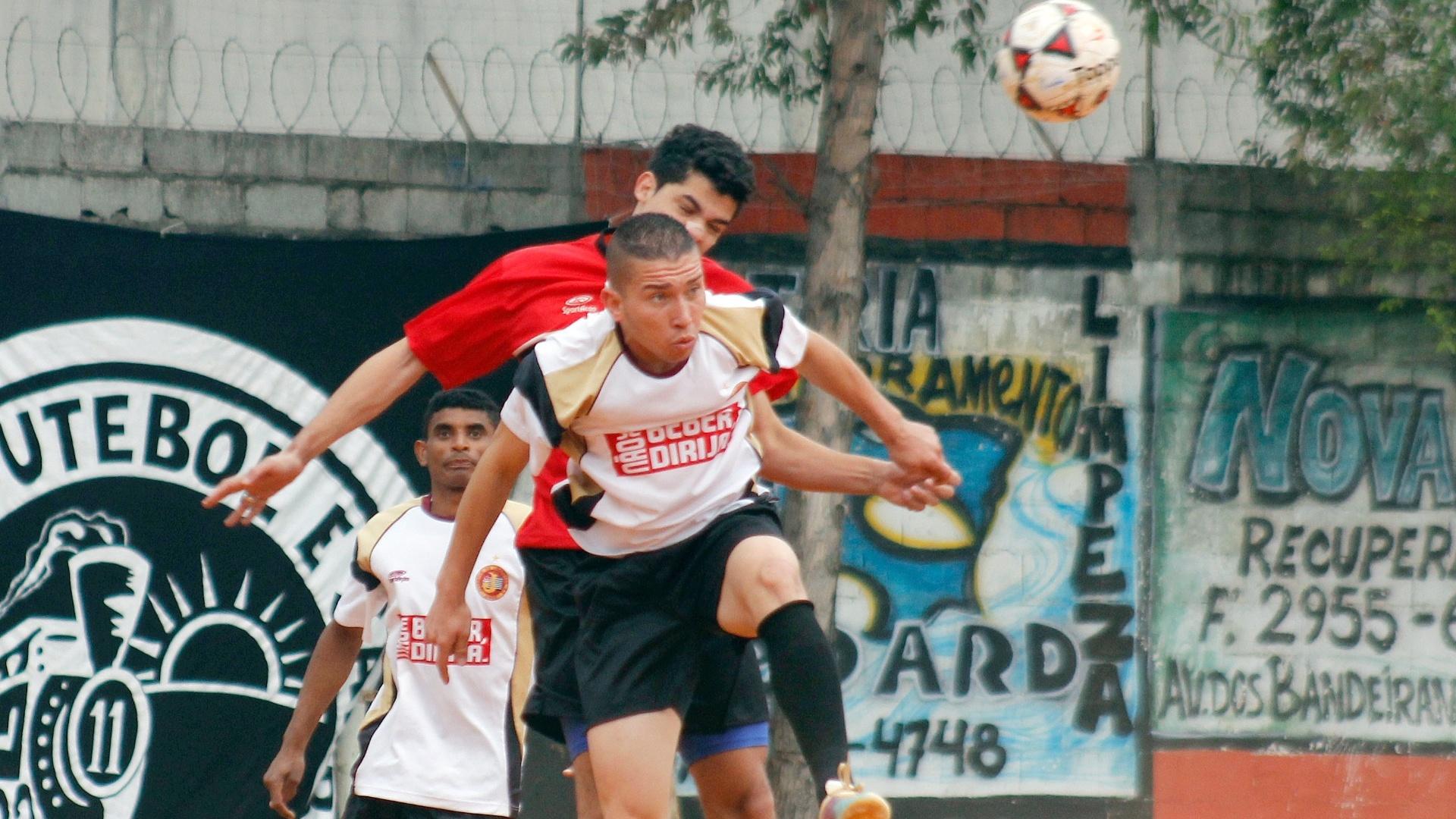 Jogadores do Juventus (branco) e do Jaçanã (vermelho) disputam bola aérea