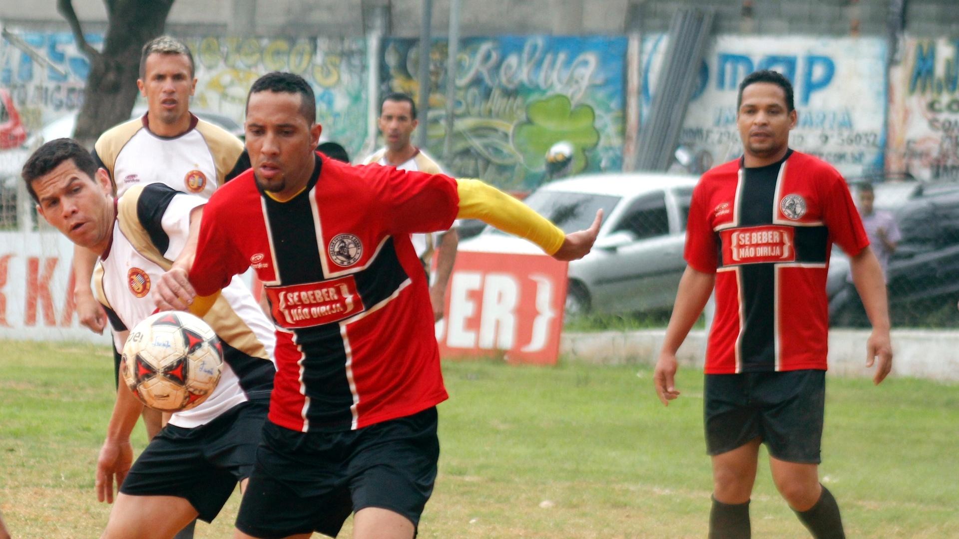 Meia do Jaçanã (vermelho) ganha jogada contra zagueiro do Juventus (branco)